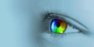 Ein Auge vor hellblauem Hintergrund mit regenbogenfarbiger Pupille sieht nach links. Bei der Video-Version öffnet und schließt sich das Auge und das Blickfeld wird noch mit einem leichten regenbogenfarbigen Lichtschein belegt.